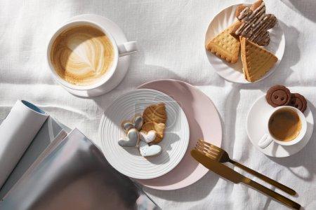 Photo pour Vue du dessus des tasses à café à côté des biscuits et des magazines sur la nappe blanche - image libre de droit
