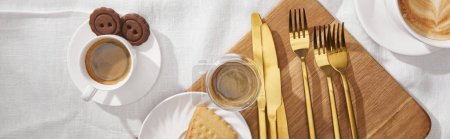 Photo for Top view of coffee and tasty cookies on chopping board on white cloth, panoramic shot - Royalty Free Image