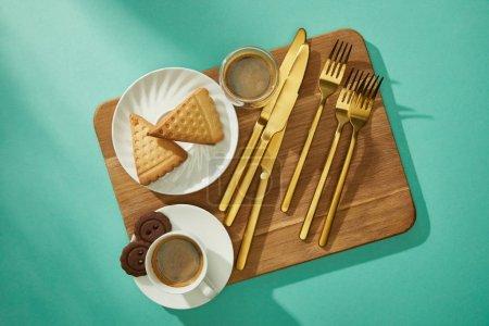 Foto de Vista superior de las galletas frescas con café y cubiertos en la tabla de picar en fondo turquesa. - Imagen libre de derechos