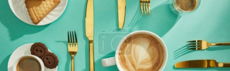 Top view of coffee with delicious cookies and cutlery on turquoise background, panoramic shot
