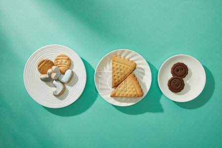 Top view of tasty cookies on plates on turquoise background