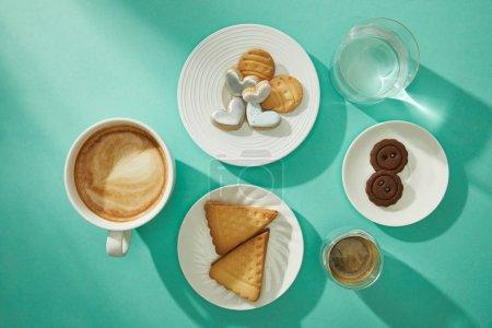 Photo pour Vue du dessus des biscuits frais avec café et verre d'eau sur fond turquoise - image libre de droit