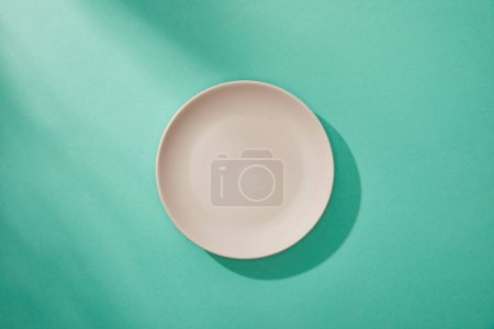 Photo for Top view of empty plate on turquoise background - Royalty Free Image