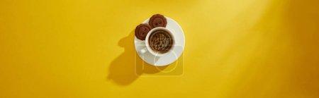 Photo pour Vue du dessus de tasse de café avec biscuits sur la soucoupe sur la surface jaune, vue panoramique - image libre de droit