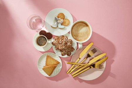 Photo pour Vue du dessus des biscuits avec glaçure, café et verre d'eau sur fond rose - image libre de droit