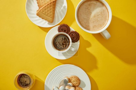Photo pour Vue du dessus des tasses et du verre de café frais avec biscuits et biscuits sur fond jaune - image libre de droit