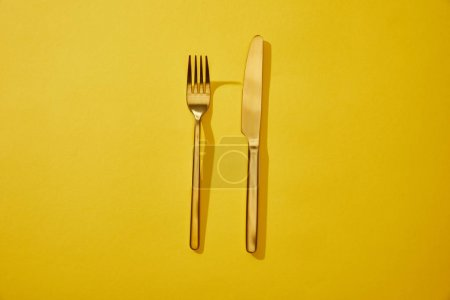 Photo for Top view of shiny fork and knife on yellow background with copy space - Royalty Free Image