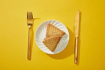 Blick von oben auf goldenes Besteck neben leckeren Keksen auf Teller auf gelbem Hintergrund