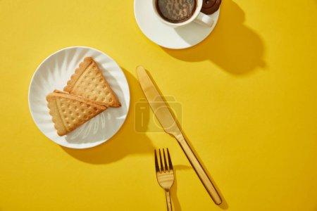 Photo pour Vue du dessus de tasse de café avec couverts dorés et délicieux biscuits sur la surface jaune - image libre de droit
