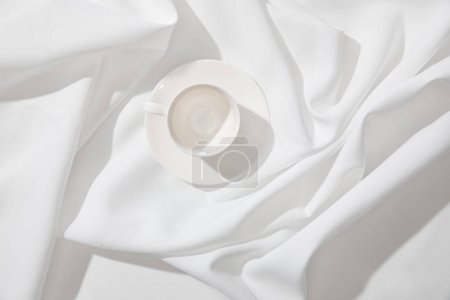 Photo for Top view of empty coffee cup with saucer on white wavy tablecloth - Royalty Free Image