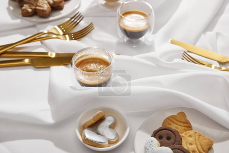 Tasty cookies and biscuits with coffee in glasses on white wavy cloth