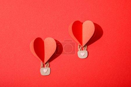 horní pohled na papírové srdce ve tvaru vzduchové balónky s zámky na červeném pozadí