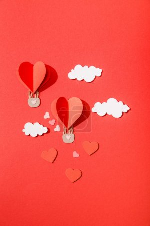 Photo for Top view of paper heart shaped air balloons in clouds on red background - Royalty Free Image