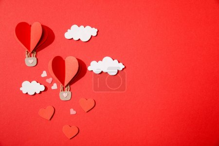 top view of paper heart shaped air balloons in clouds on red background