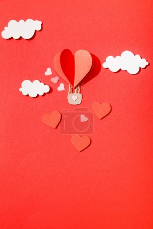 top view of paper heart shaped air balloon in clouds on red background