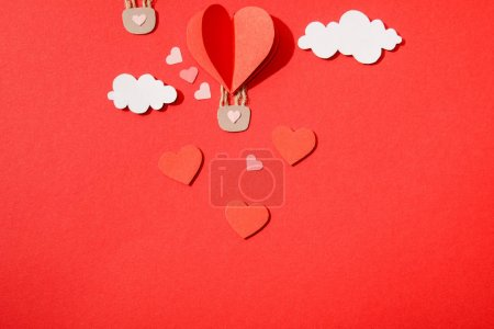 Photo for Top view of paper heart shaped air balloon in clouds on red background - Royalty Free Image