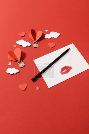 Photo for Paper clouds and heart shaped air balloons, envelope with lip print and pencil on red background - Royalty Free Image