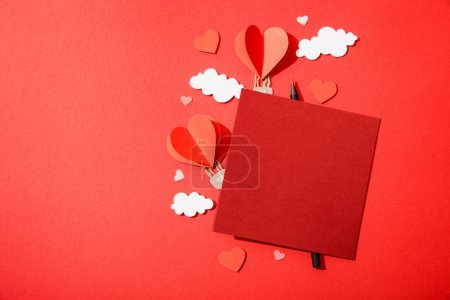 Photo for Top view of paper heart shaped air balloons in clouds near blank card and pencil on red background - Royalty Free Image