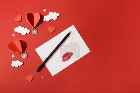 Photo for Top view of paper clouds and heart shaped air balloons, envelope with lip print and pencil on red background - Royalty Free Image