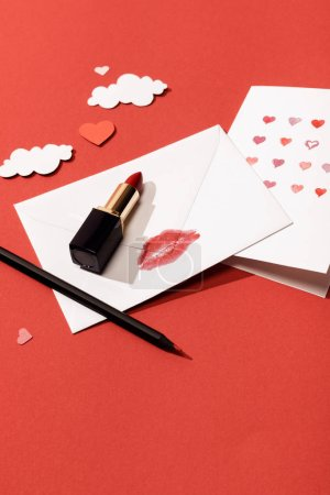 Photo for Paper clouds and hearts, greeting card near envelope with lip print, lipstick and pencil on red background - Royalty Free Image