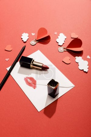 Photo for Paper clouds and heart shaped air balloons, envelope with lip print, lipstick and pencil on red background - Royalty Free Image