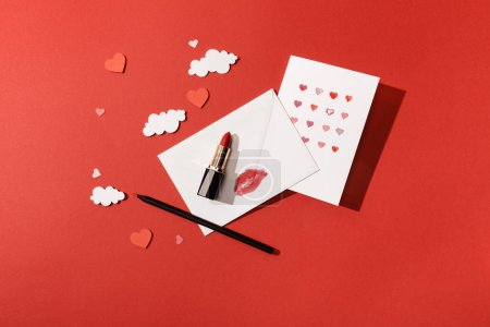 Photo for Top view of paper clouds and hearts, greeting card near envelope with lip print, lipstick and pencil on red background - Royalty Free Image