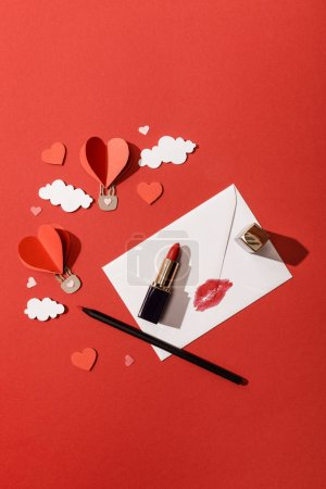 Photo for Top view of paper clouds and heart shaped air balloons, envelope with lip print, lipstick and pencil on red background - Royalty Free Image