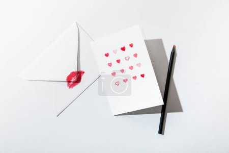 Photo for Top view of greeting card with hearts near envelope with lip print and pencil on white background - Royalty Free Image