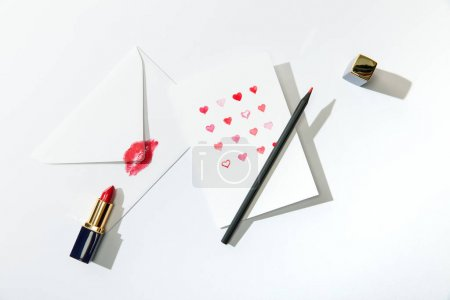 Photo for Top view of greeting card with hearts near envelope with lip print, lipstick and pencil on white background - Royalty Free Image