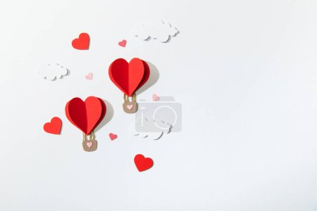 Photo for Top view of paper heart shaped air balloons in clouds on white background - Royalty Free Image
