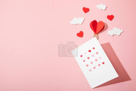 Photo for Top view of greeting card with hearts in white envelope near paper heart shaped air balloon in clouds on pink - Royalty Free Image