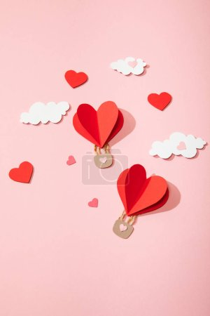 top view of paper heart shaped air balloons in clouds on pink
