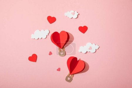 Photo pour Top view of paper heart shaped air balloons in clouds on pink - image libre de droit