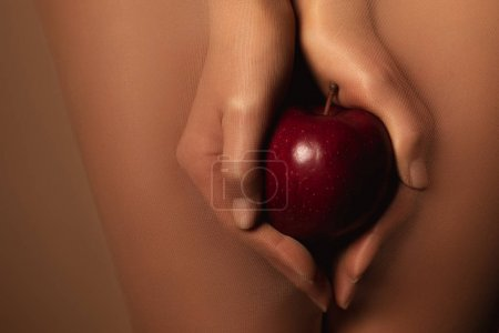 Photo for Cropped view of woman in nylon tights holding ripe red apple isolated on brown - Royalty Free Image