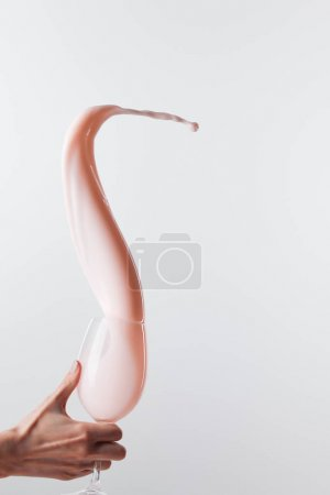 Photo pour Cropped view of woman holding glass with fresh pink milk smooth splash isolated on white - image libre de droit
