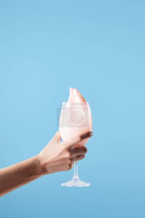 Photo pour Cropping view of woman holding glass with fresh pink milk splash isolated on blue - image libre de droit