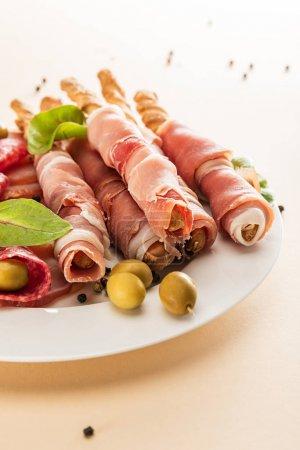 Photo pour Délicieux plateau de viande servi avec des olives et des bâtonnets sur fond beige - image libre de droit