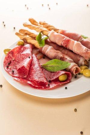 köstliche Fleischplatte serviert mit Oliven und Semmelstangen auf Teller auf beigem Hintergrund