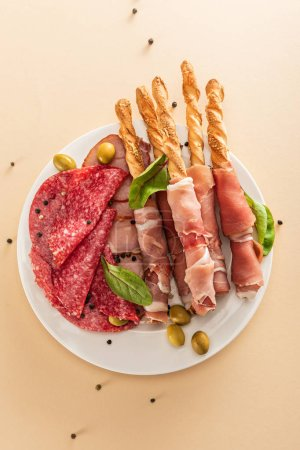 Photo for Top view of delicious meat platter served with olives and breadsticks on plate on beige background - Royalty Free Image