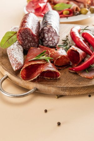 Photo for Delicious meat platters served with rosemary and chili pepper on wooden board on beige background - Royalty Free Image