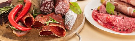 Photo for Delicious meat platters served with olives, spices on plate and wooden board on beige background, panoramic shot - Royalty Free Image
