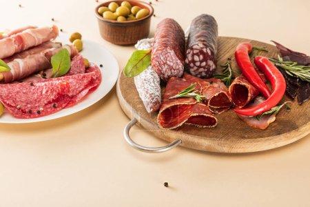 Foto de Deliciosos platos de carne servidos con aceitunas, especias en platos y tableros de madera de fondo beige. - Imagen libre de derechos