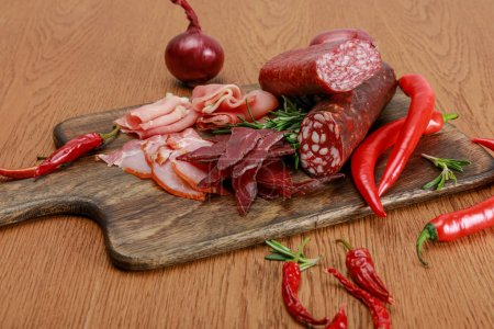 Photo for Delicious meat platter served with chili pepper and rosemary on wooden table - Royalty Free Image