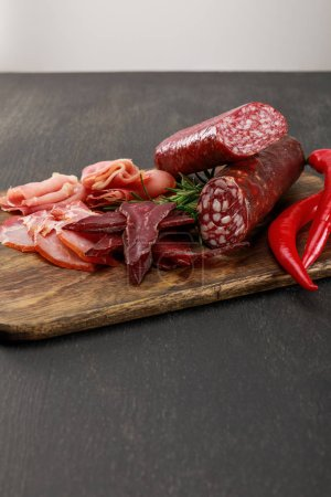 Photo for Delicious meat platter served with chili pepper and rosemary on wooden black table - Royalty Free Image