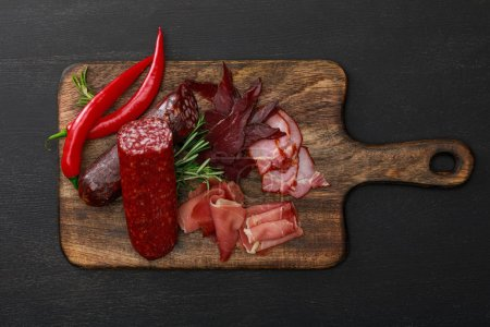 Photo for Top view of delicious meat platter served with chili pepper and rosemary on wooden black table - Royalty Free Image