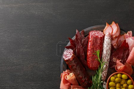 Photo for Top view of delicious meat platter served with olives and herbs on wooden black table - Royalty Free Image