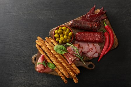 Photo for Top view of delicious meat platters served with olives, breadsticks and herbs on boards on wooden black table - Royalty Free Image