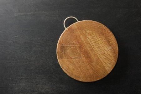 Foto de Vista superior del tablero de corte vacío en la mesa negra de madera - Imagen libre de derechos