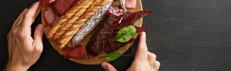 Photo for Cropped view of man holding delicious meat platter served with breadsticks and herbs on board on wooden black table, panoramic shot - Royalty Free Image
