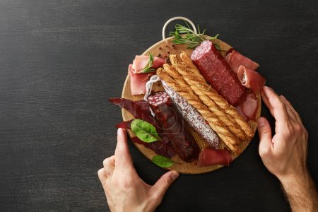 Photo for Cropped view of man holding delicious meat platter served with breadsticks and herbs on board on wooden black table - Royalty Free Image
